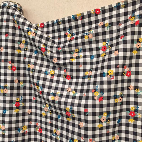 A black and white gingham fabric that has colorful flowers on it