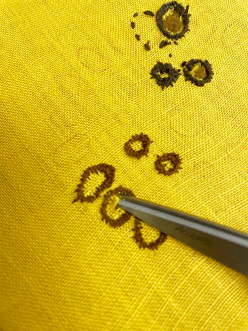 Using scissors to cut out the center of embroidered eyelets