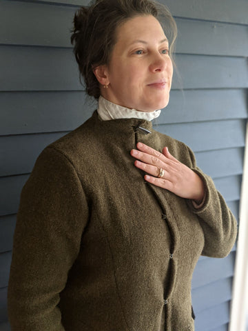 woman standing by the side of a house wearing a brown wool coat.