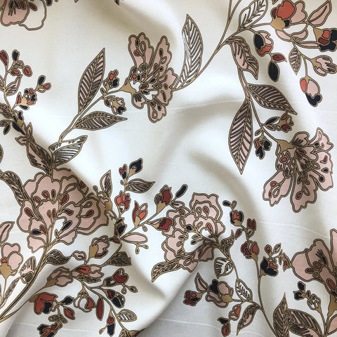 Silk crepe de chine fabric photo.  Off white background with pink floral accent print.