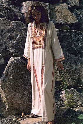 Woman in a white Gaza Dress (thobe) with red embroidery standing by boulders