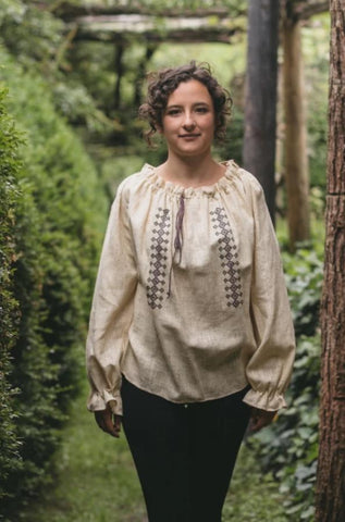 Young woman walking towards camera outdoors with greenery surrounding her. She is wearing 103 Romanian Blouse. Blouse is natural linen with traditional embroidery.  Paired with plain black pants.