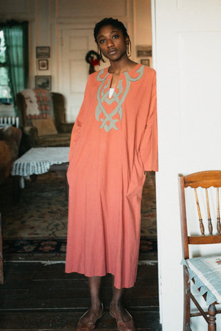 Young african american woman wearing long coral color version of 104 Egyptian shirt.  Shirt has grey applique around neck and on front yoke of top.  Model is leaning on door frame looking towards camera with hands in pockets.