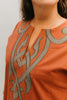 Woman in coral Egyptian Shirt.  Close up of front yoke with neck slit and gray applique.
