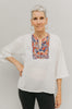 Older woman in short version of Egyptian top.  Top is made in a white gauze fabric with multi-colored embroidery on yoke.  Model has one hand on hip and poses with white backdrop.