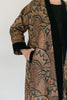 Close up of Turkish coat with view of side pocket.  Model has hand partially in pocket.