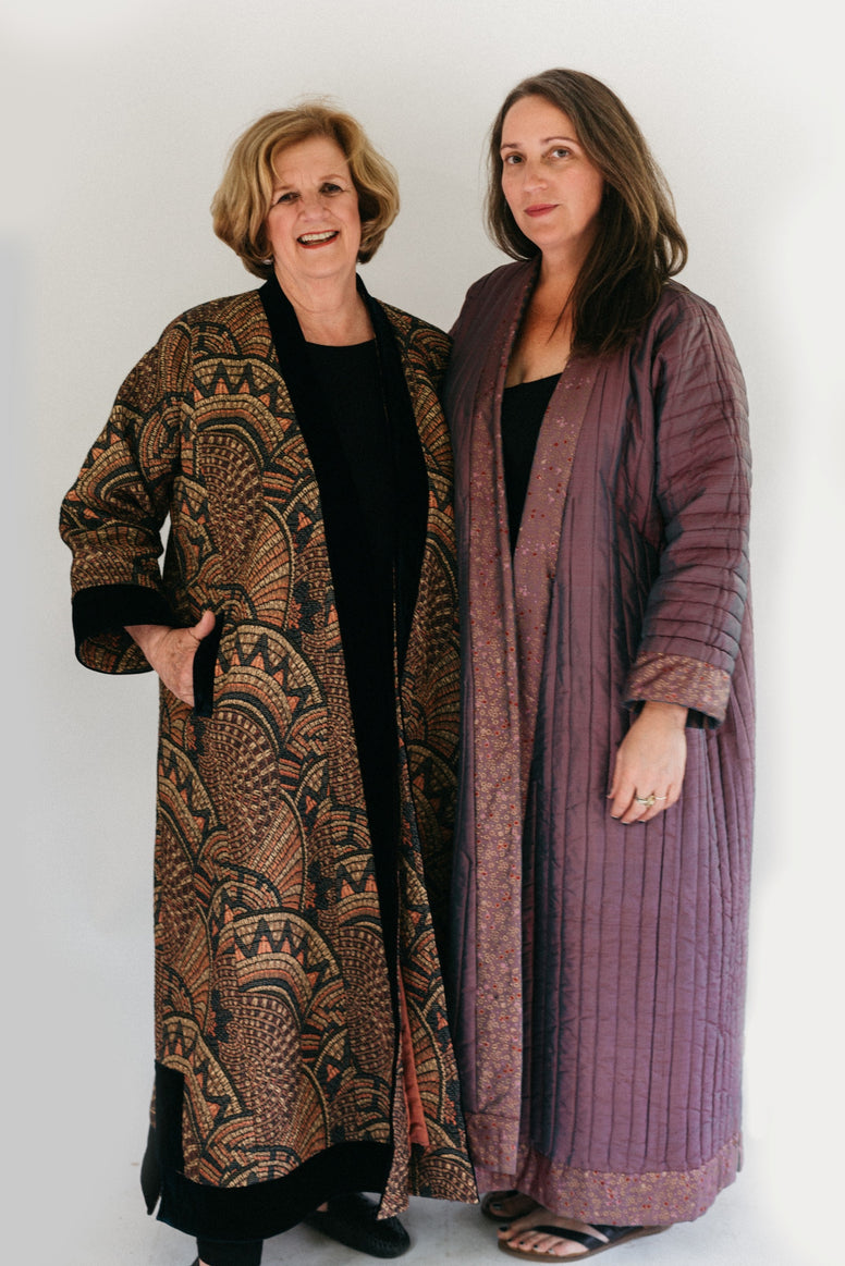 Photograph of two women standing side by side.  Woman on the left is wearing a tapestry fabric Turkish coat with trapunto trim around sleeves, front opening and bottom hem. Woman on right is wearing a solid lavandar silk coat with trapunto stitching all over the body of coat.