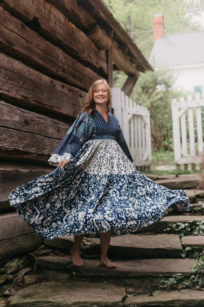 Woman twirling with full skirt in mid air.  Dress is multi fabrics all are various blue and white floral prints.  Woman is on stone stairs outdoors with wooden building behind her.