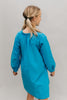 Photo of young girl wearing a blue corduroy Smock. Model had back to camera.  Photo shows gathering at neckline and back view.