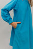 Photo of young girl wearing a blue corduroy Smock. Photo shows close up of sleeve cuff and side seam. Girl has her hand in the pocket at side.