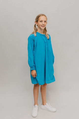 Photo of young girl wearing a blue corduroy Smock.  Model is standing in front of a white background looking towards camera.