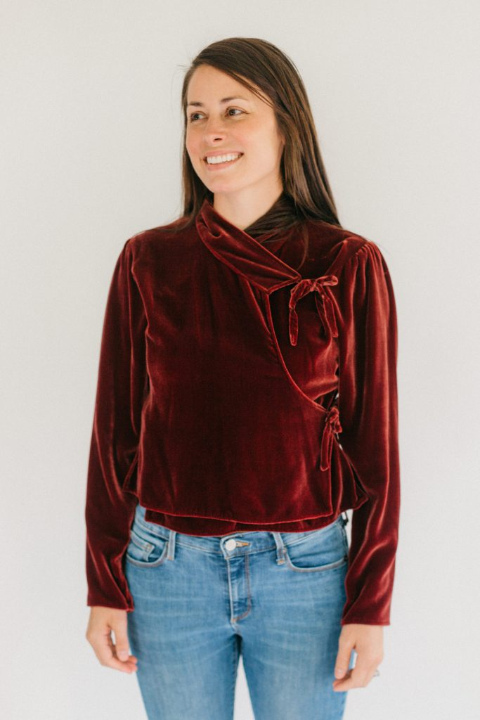 Woman in red velvet Nepali Top. Wearing jeans standing in front of white background.