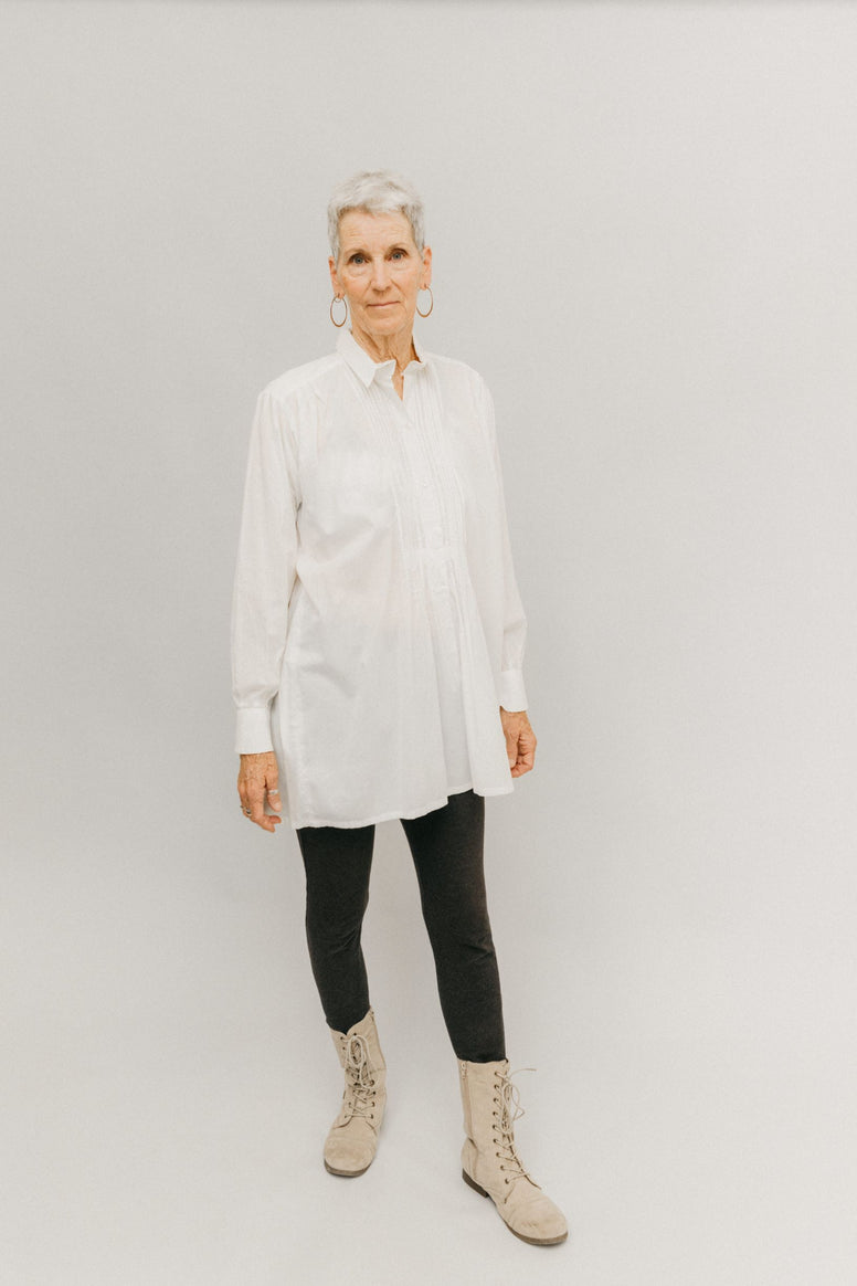 Woman standing in front of light grey background wearing a white Croatian shirt as a tunic with black leggings and boots.