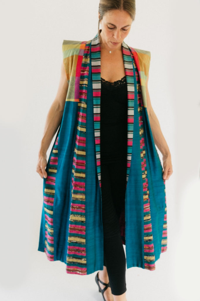 Woman wearing multi colored 118 Tibetan Panel coat.  Standing in front of white background holding sides out in hands.  coat is primarially blue with multicolored shoulders and trim.