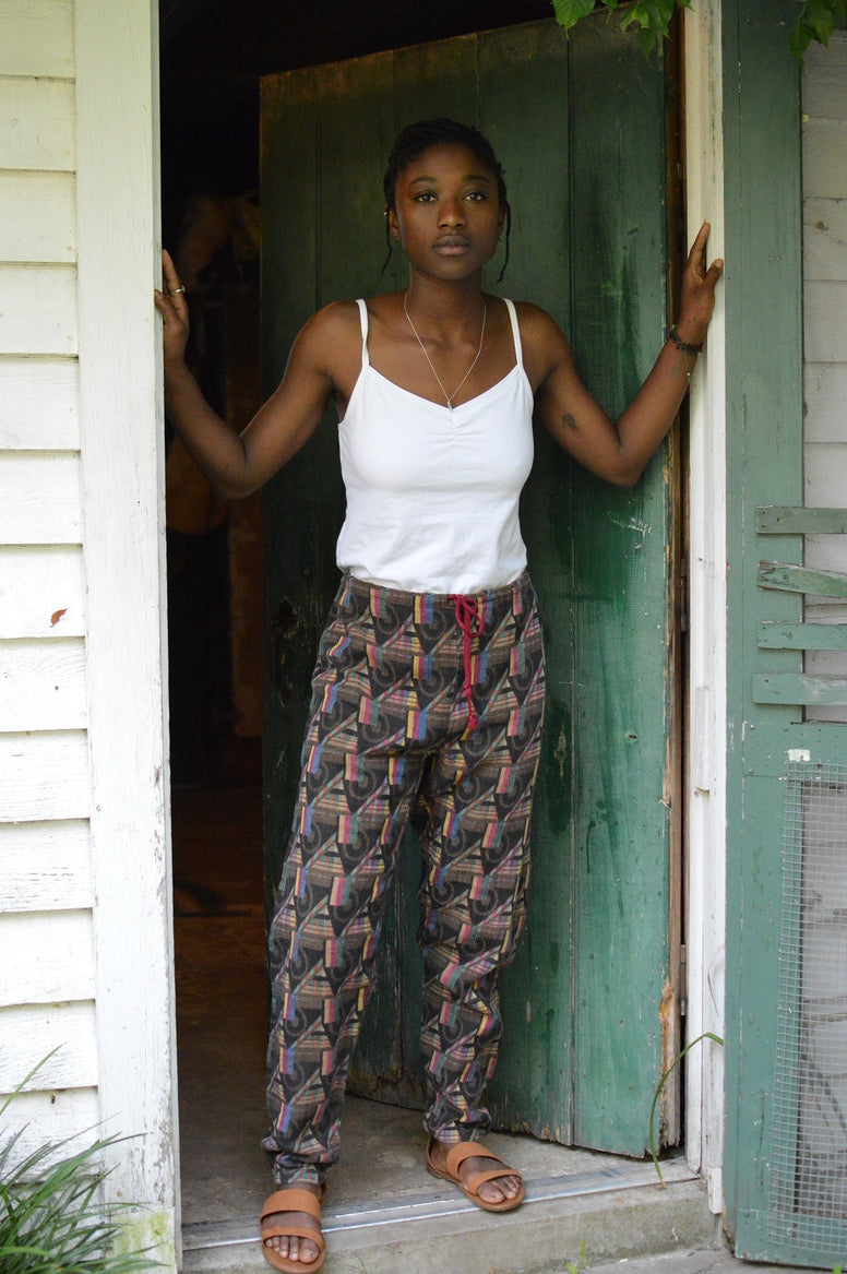 Young African American woman standing in a doorway wearing 119 Sarouelle pants view B (African Pants)