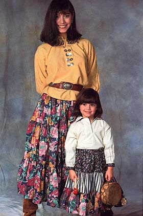 Woman and Child wearing 120 Navajo Blouse and Skirt.  Child is standing in front of woman holding a small drum.