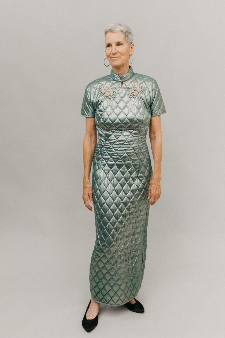 Photo of woman in ankle length 122 Hong Kong Cheongsam.  Fabric is a quilted shinny light green with ornate metallic frog closures.