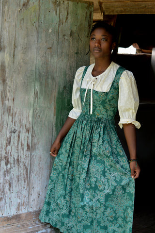 Young woman wearing green Dirndel (View B dress with View A Blouse).  She is standing in front of a wood door holding skirt in both hands by her side.