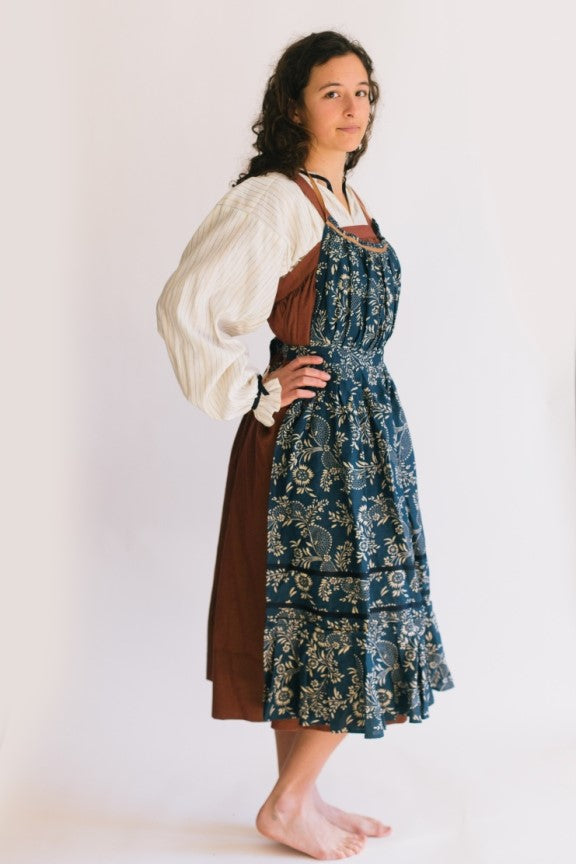 Model wearing Russian settlers outfit.  Blouse is worn under jumper and apron is worn over the jumper.