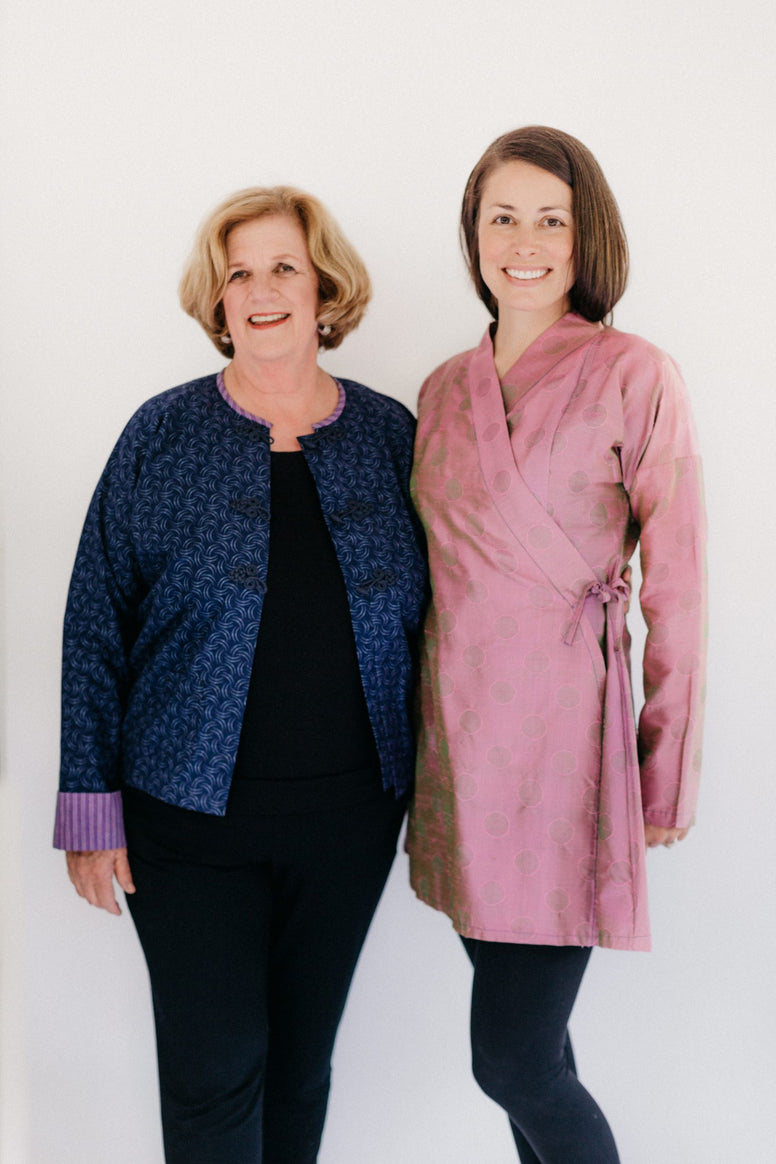 Two women modeling the Burmese Jacket (on left) and the Thai Blouse (right).  Burmese Jacket is unbuttoned in front and Thai Jacket is a lengthened adaptation.