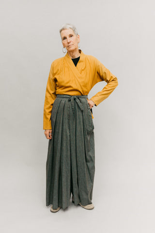 Photo of woman wearing Hakama pants.  Standing in front of a studio backdrop.  Left hand on hip.