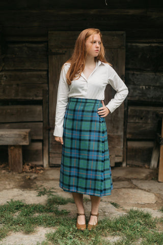 Photo of a young woman standing outdoors wearing the kilt skirt.