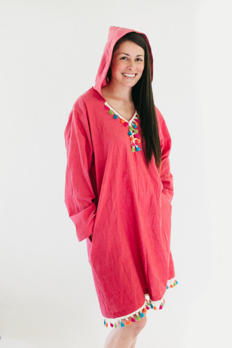 brunette white woman smiling, standing in front of a white studio backdrop, wearing the #157 Moroccan Djellaba pullover with hands in pockets.
