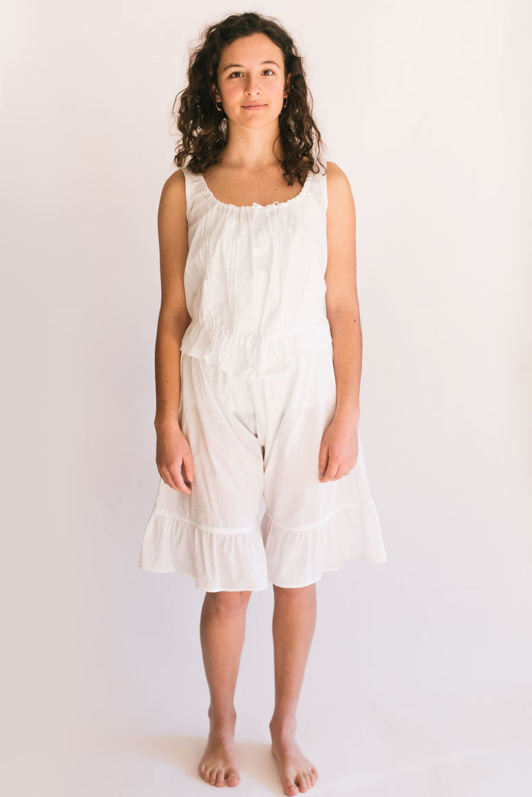 Photo of young woman standing in front of a white studio backdrop wearing camisole and drawers.