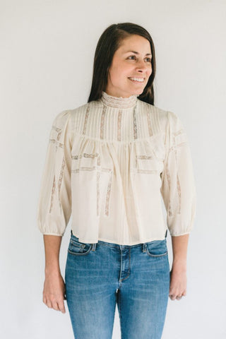 Brunette woman smiling, standing in front of a white studio backdrop wearing 206 Gibson Girl Blouse.