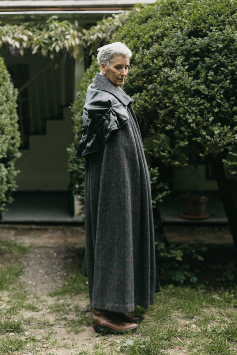 Older white woman with short gray hair standing surrounded by greenery turned to the side wearing 207 Kinsale Cloak with hood down over shoulders.