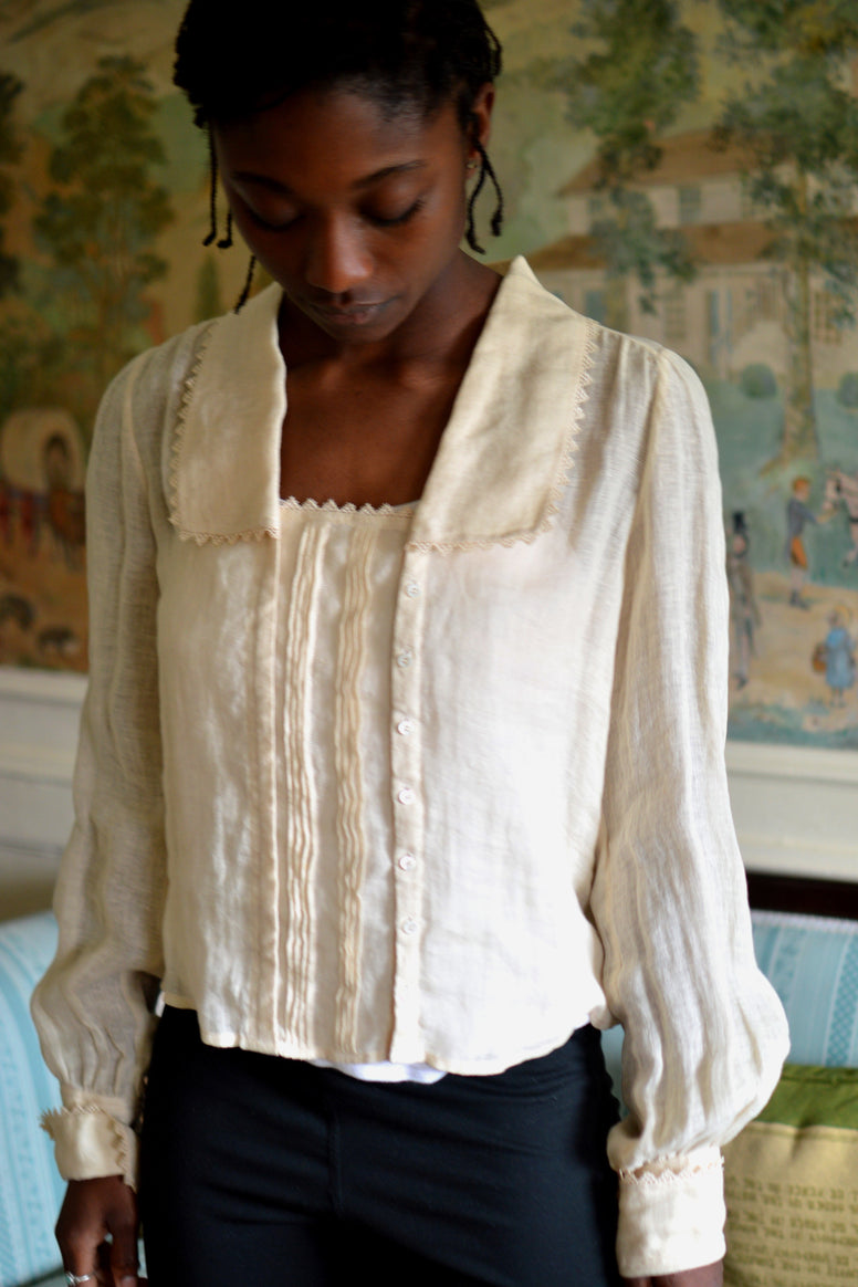 African woman standing in a room looking down wearing 210 Armistice Blouse., and black leggings.