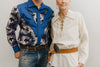 A man and a older woman standing in front of a white studio backdrop ,wearing 212 Five Frontier Shirts. Man wearing View D with decorative bull's head yoke and woman wearing View A with lace up front with belt around the waist.