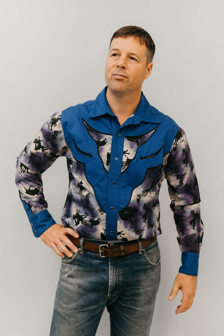 Man with hand on hip standing in front of a white studio backdrop wearing 212 Five Frontier Shirt View D with decorative bull's head yoke.