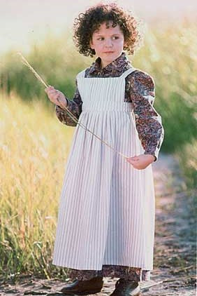 Small curly haired child standing surrounded by green grass holding a long blade of grass wearing 213 Child's Prairie Dress and Pinafore.