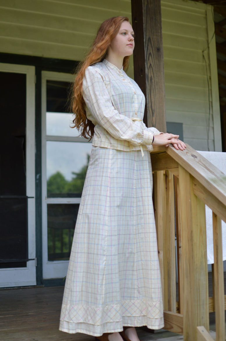 Young red head woman standing on a porch wearing 216 Schoolmistresses Shirtwaist and Skirt.