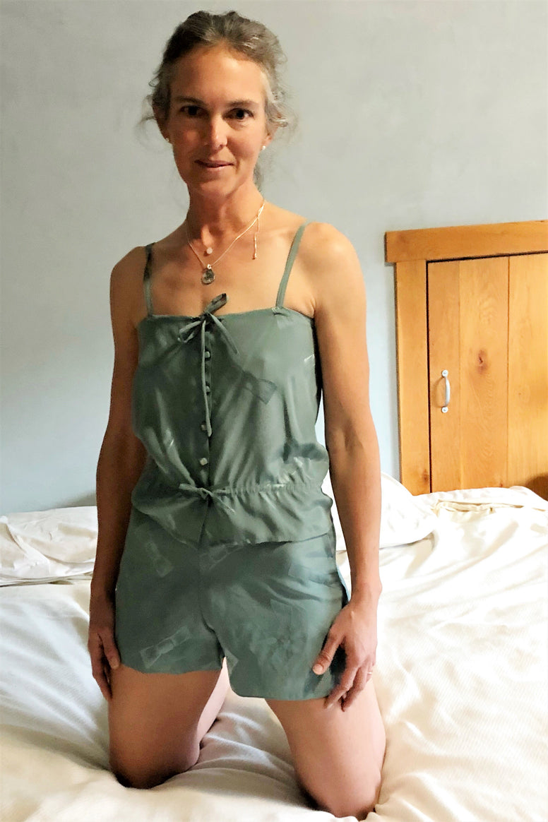 Woman kneeling on bed wearing 219 Intimacies camisole and tap pants.