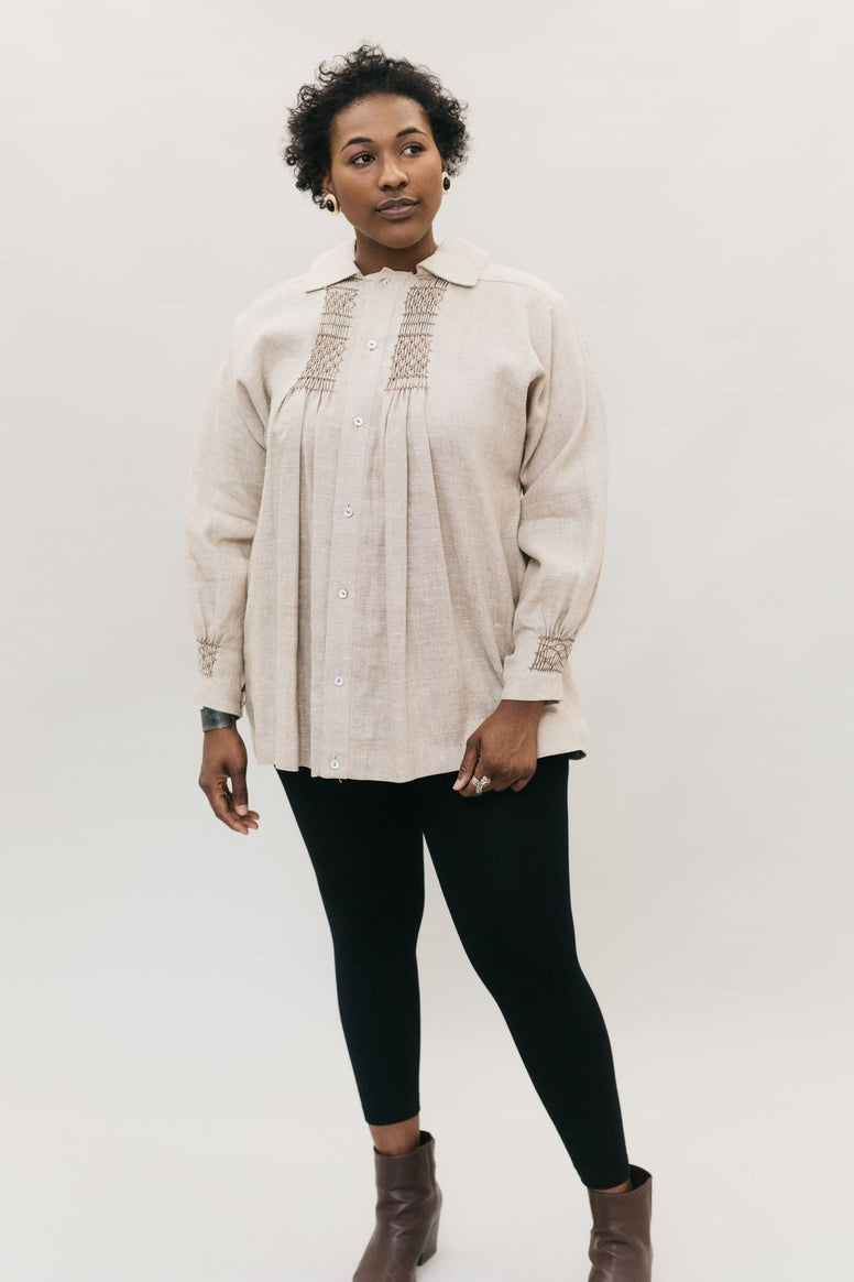 Young African American woman standing in front of a white studio backdrop looking right, wearing 221 English Smock.