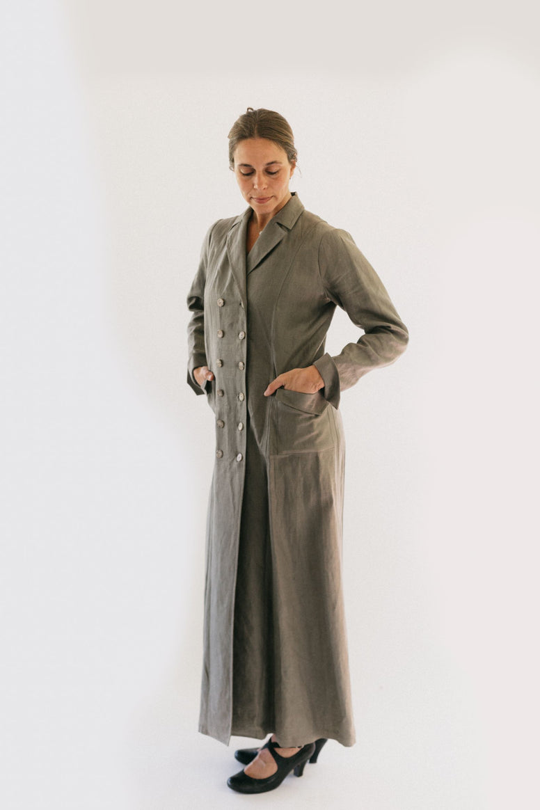 Woman wearing standing in front of a white studio backdrop looking down with hands in pockets wearing 230 Model T Duster