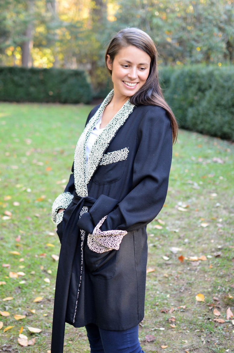 Young brunette white woman smiling down turned to the left and standing surrounded by greenery wearing the 238 Le Smoking Jacket with hands in pockets with quilted lapel and cuffs and pocket band, with sash wrapped around the waist.