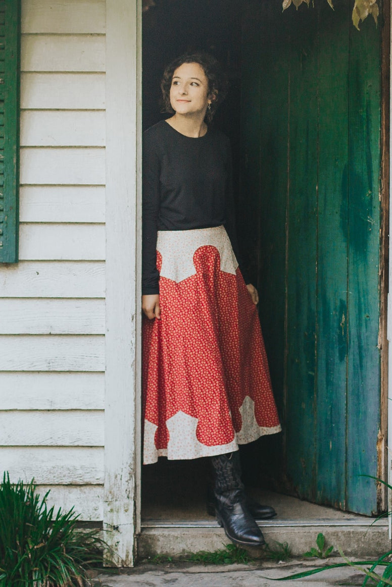 Young brunette white woman standing in a doorway looking to her left wearing 243 Rodeo Cowgirl skirt and black boots