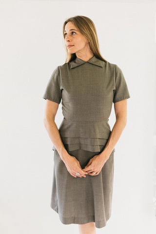 Woman standing with hands in front of her looking to the side in a tan colored version of #249 1930s Day Dress.  She is wearing view A. View A features round neck with collar points and peplum cleverly cut on the straight grain but with the slimming look of a bias cut.