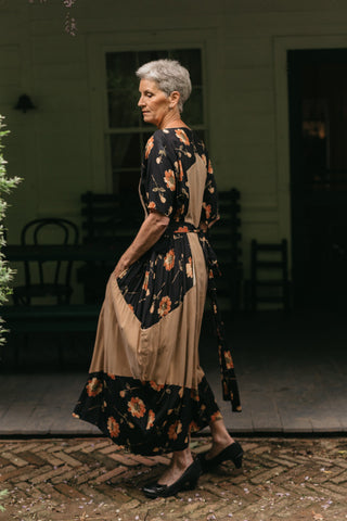 Older White woman with grey hair, wearing #261 Paris Promenade Dress, turned to the side standing in front of a porch.
