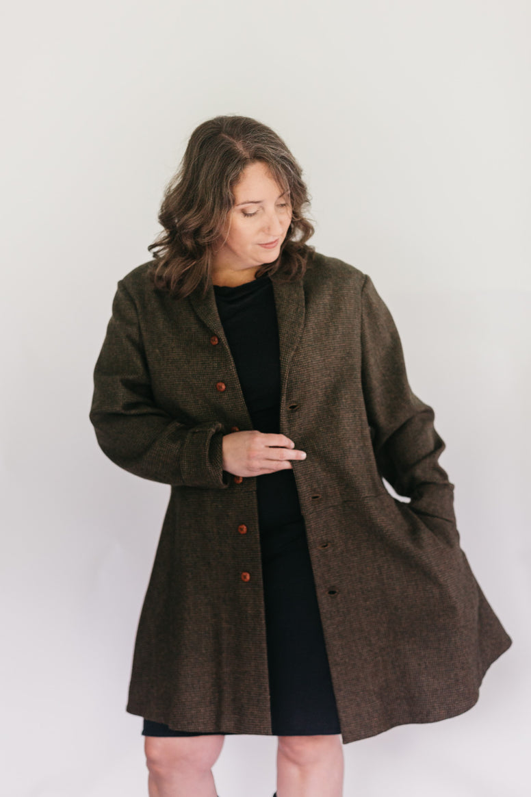 Brunette White woman standing in front of a studio white backdrop wearing a black dress under the #263 Countryside Frock Coat with her left hand in the pocket.