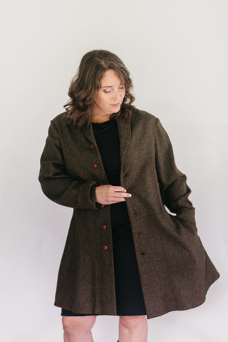 Burnett White woman standing in front of a studio white backdrop wearing a black dress under the #263 Countryside Frock Coat with her left hand in the pocket.