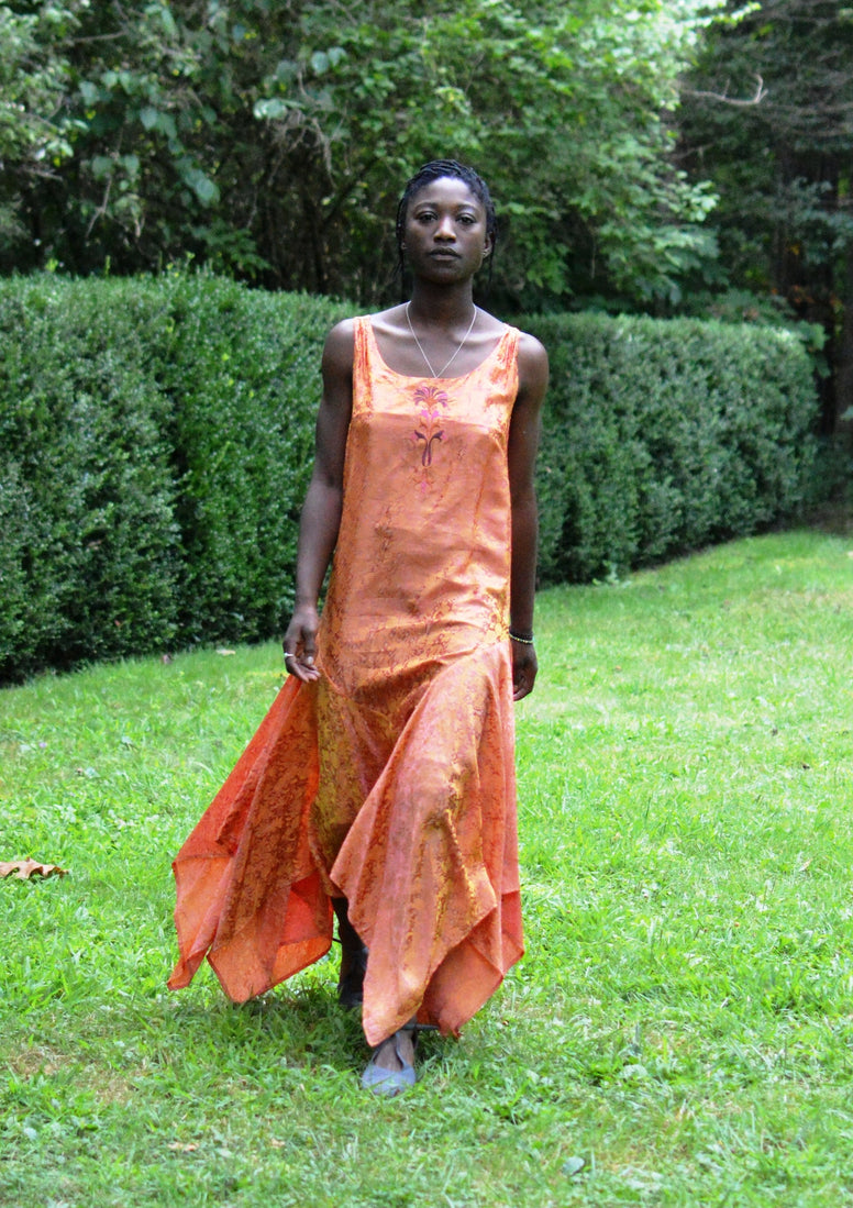 Young African woman standing surrounded by greenery wearing #264 Monte Carlo Dress in orange.