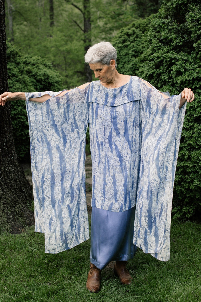 Older White woman with grey short hair standing surrounded by greenery looking down, wearing the #266 Greek Island Dress Tunic, extending both arms out showing the free-floating sleeve panels.
