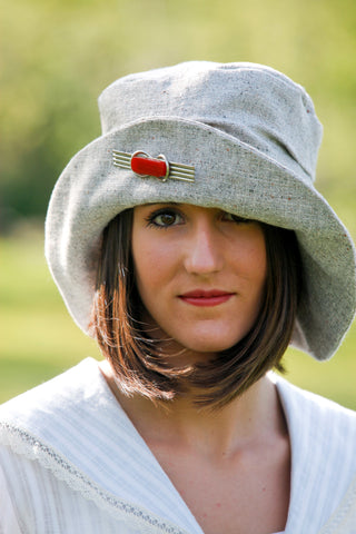 Young Burnett white women wearing red lipstick. Wearing the #269 Metropolitan Hat in gray with a red brooch on the brim of the hat.