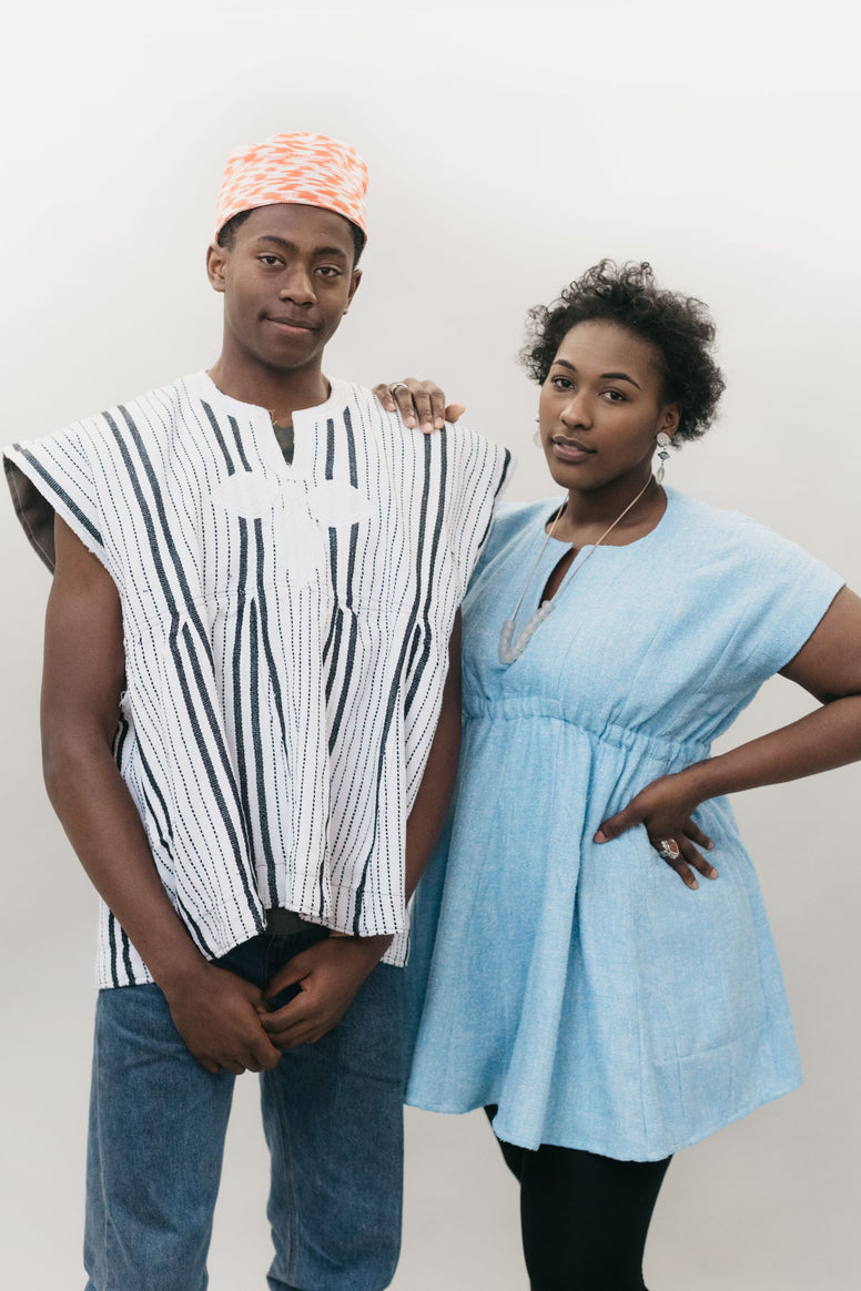 An African American young man and women standing in front of a white studio backdrop wearing the Ghanaian Smock.