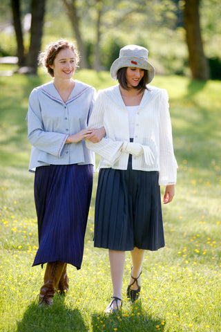 Two  women walking linking arms, surrounded by greenery. Woman on the left wearing #270 Metro Middy Blouse in blue and long skirt. Woman on the right is wearing a hat with the Metro Middy Blouse in white and a knee length skirt.