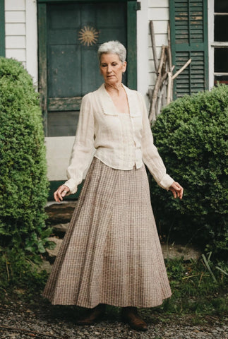 Older woman standing in front of a door with arms our surrounded by greenery wearing 210 Armistice Blouse and 209 Walking Skirt.